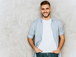 Portrait of handsome smiling hipster lumbersexual businessman model wearing casual shirt clothes. Fashion stylish man posing against gray wall