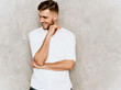 Portrait of handsome smiling hipster lumbersexual businessman model wearing casual summer white shirt. Fashion stylish man posing against gray wall