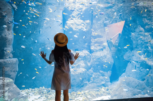Canvas woman near big aquarium with fishes