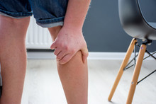 Human, Who Had Been Elevated From Chair, Holding His Palm Over Calf Or Gastrocnemius Muscle, Which Grabbed Cramp With Severe Pain. Concept Images Illustrating Human Reaction To Pain Symptom In Calf