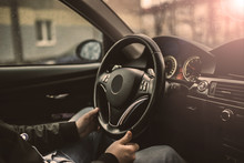 Driver's Hands Hold The Steering Wheel Of A Modern Car While Waiting For A Passenger.