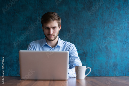 Fototapeta Happy young businessman using laptop at his office desk. obraz na płótnie