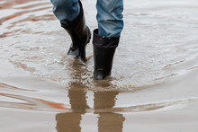 A Man In Rubber Boots Walks Through A Muddy Puddle