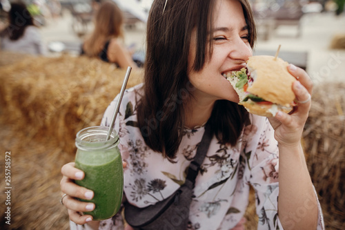Fotografia, Obraz Stylish hipster girl in sunglasses eating delicious vegan burger and holding smoothie in glass jar in hands at street food festival
