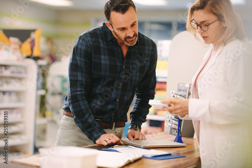 Photo sur Toile Pharmacie Pharmacist showing medicine to customer in pharmacy
