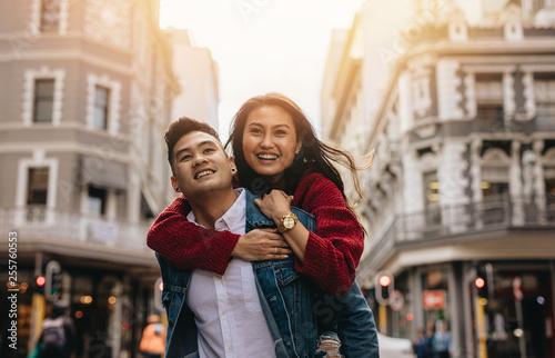 Foto  Asian couple piggybacking on city street