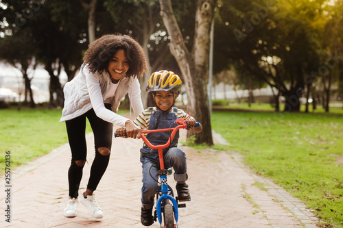 Mother teaching son to ride bicycle Canvas-taulu