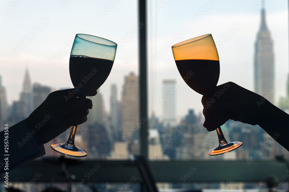 Fototapety, obrazy: Man and female toasting with glasses of red wine in the apartment with New York city view.