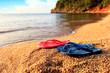 Beach slippers lie on a stone near the transparent sea