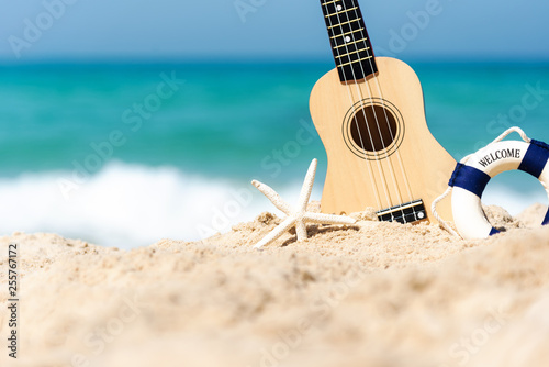 The Summer day with Guitar ukulele for relax on the beautiful beach and blue sky background, copy space. Travel and Summer Concept