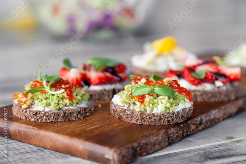 Сloseup macro set of different northern trendy appetizers on smorrebrod rye bread with red caviar and avocado, strawberries, balsamic dressing. Concept quick snack in wine bar, food shooting