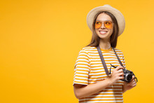 Tourism Concept. Horizontal Banner Of Excited Young Female Tourist Holding Photo Camera, Isolated On Yellow Background With Copy Space