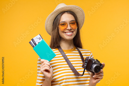 Fototapeta Excited cheerful young tourist girl holding passport with tickets and camera, isolated on yellow background obraz