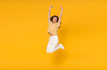 Cheerful Happy Girl Jumping In The Air With Raised Fists If She Is Winner, Isolated On Yellow Background