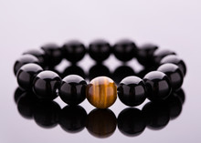 Stone Bead Bracelets Handmade From Lucky Stones. Bracelet From Black Round Stones Lying On A Mirror Surface.