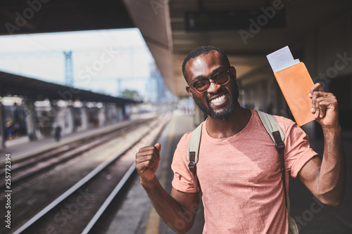 Photo  Celebrating smiling man holding tickets in his hand