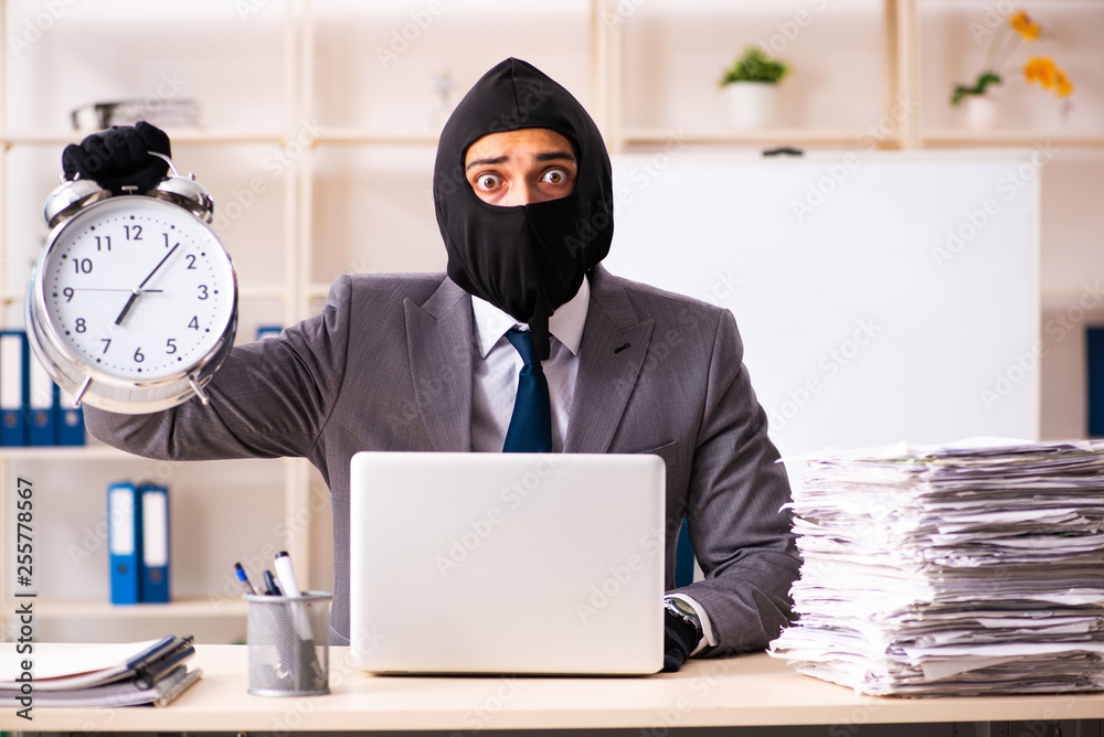 Fototapeta Male gangster stealing information from the office
