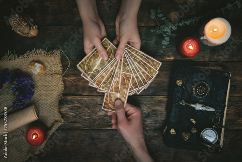 Tarot cards, magic book and fortune teller hands on a wooden table background Fotobehang