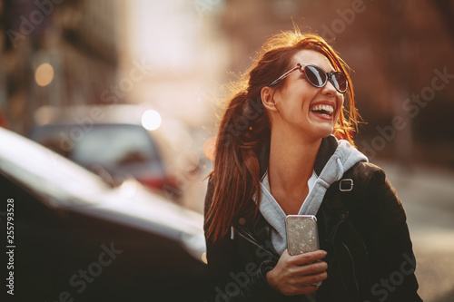 obraz dibond Young happy woman on the street in the city