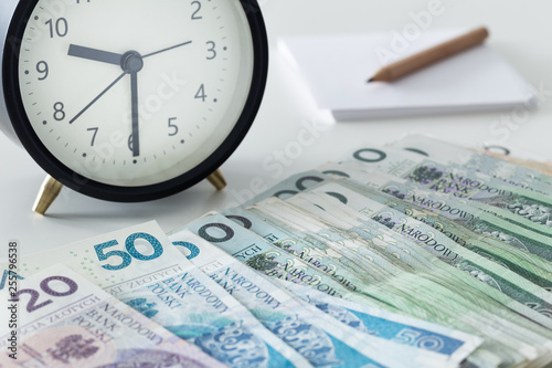 Fototapeta Polish money, zloty, with an alarm clock a page and a pencil obraz