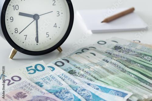 Obraz na płótnie Polish money, zloty, with an alarm clock a page and a pencil