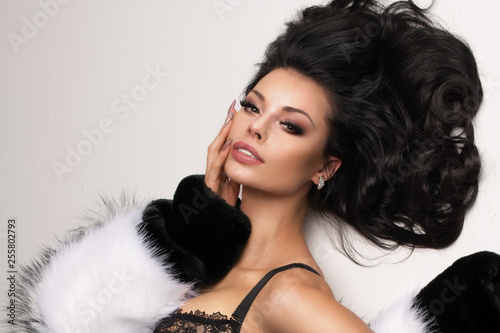 b0e2bdd3ebc Fashion portrait of elegant brunnette women in studio lying over white  background wearing black lingerie