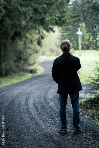 Photo  Young man standing on road at end of dark forest