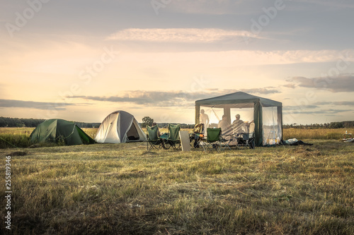 Stampa su Tela Camping site camping tents on summer field sunset sky during camping holidays