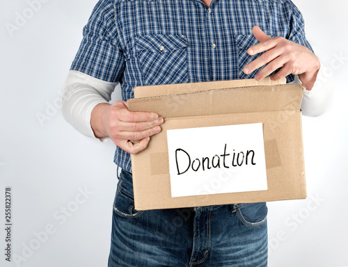Fotografie, Obraz  man in a blue checkered shirt and jeans holds a big brown paper box with the ins