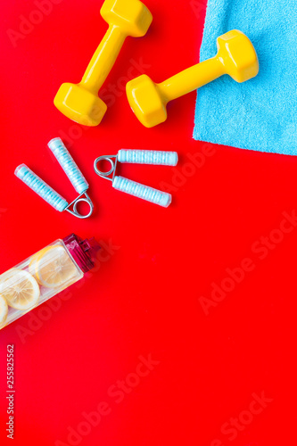 Fotografía  Fitness set with bars, towel, bottle of water and wrist builder on red backgroun