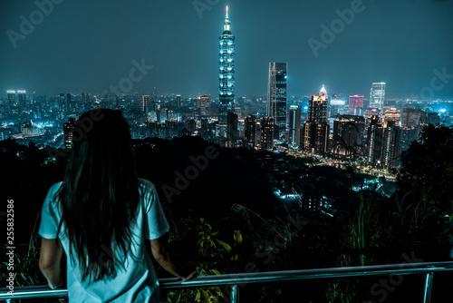 A woman overlooks the skyline of Taipei at night.  Taiwan. Wallpaper Mural