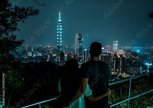 A couple overlooks the bright skyline of Taipei at night.  Capital city of Taiwan