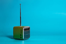 Small Green Radio On A Blue Background. The Concept Of Listening To Music, Listening To The Radio.