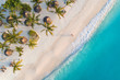 Leinwanddruck Bild - Aerial view of umbrellas, palms on the sandy beach of Indian Ocean at sunset. Summer holiday in Zanzibar, Africa. Tropical landscape with palm trees, parasols, white sand, blue water, waves. Top view