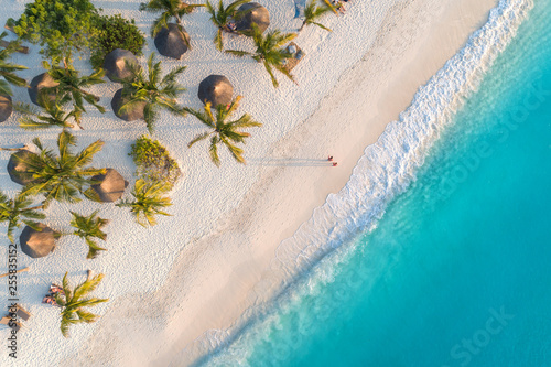 Aerial view of umbrellas, palms on the sandy beach of Indian Ocean at sunset. Summer holiday in Zanzibar, Africa. Tropical landscape with palm trees, parasols, white sand, blue water, waves. Top view