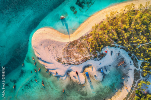 Valokuva Aerial view of the fishing boats on tropical sea coast with sandy beach and palms at sunset