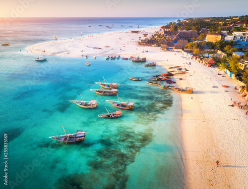 Poster Zanzibar Aerial view of the fishing boats on tropical sea coast with sandy beach at sunset. Summer holiday on Indian Ocean, Zanzibar, Africa. Landscape with boat, buildings, transparent blue water. Top view