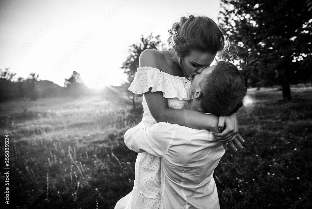 Fototapeta Black and white photo of a kissing couple in love, the guy turns his beautiful girl in his arms