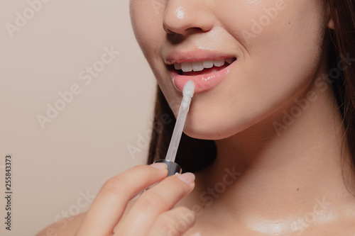 Foto Applying transparent lip gloss