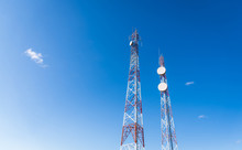 Colorful Mobile Phone Network Telecommunication Towers Against Blue Sky Background. Concept Of Telecom, Telco, Connectivity, And Technology