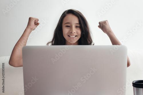 retrato de niña sonrriente con los brazos arriba viendo su laptop Canvas-taulu