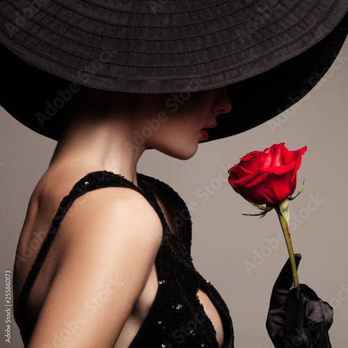 Beautiful woman in hat and red rose. Wall mural