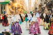 Several of the thousands of women Falleras who parade down the street of La Paz with their typical Valencian Spanish dresses during the offering of Fallas to the Virgin, seen from behind.