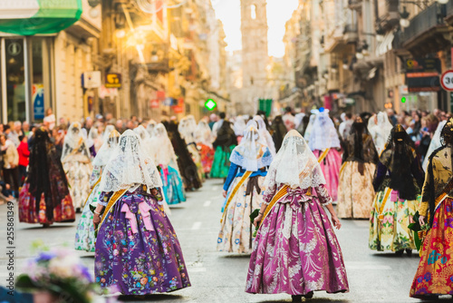 Several of the thousands of women Falleras who parade down the street of La Paz with their typical Valencian Spanish dresses during the offering of Fallas to the Virgin, seen from behind Canvas-taulu