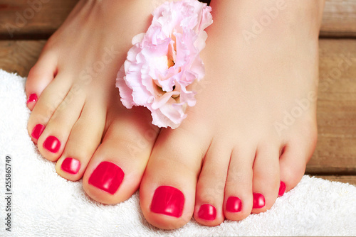 Foto auf Gartenposter Pediküre Pink pedicure with flower close-up, isolated on a wooden background, top view