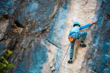 A Child Climber Climbs On A Rock.