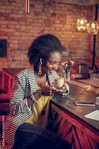 Fotografie, Obraz  Charming African-American lady having coffee sitting at bar counter