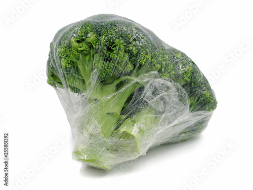 Fotografía  Broccoli wrapped in plastic foil isolated on white background