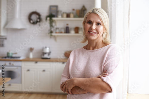 Photographie  Attractive middle aged housewife with blonde hair and brown eyes posing indoors