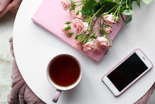 Cup Of Hot Tea With Mobile Phone, Flowers And Book On White Table